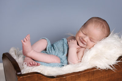 Beautiful Mississippi Newborn Photography: sleeping newborn boy smiling while wrapped in blue in a wooden cradle