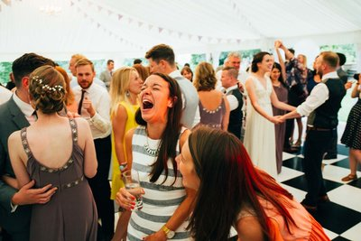 Laughing natural wedding guest photograph on the dance floor inside a marquee reception