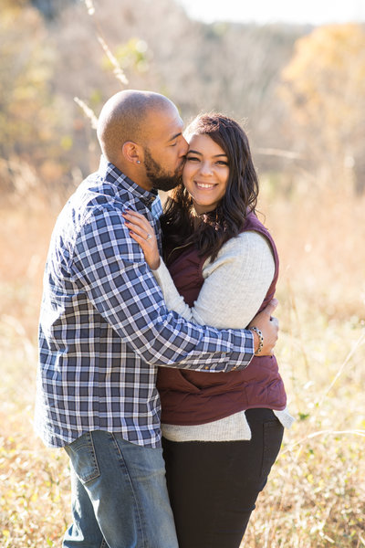 Engagement photo of man kissing fiance on the cheek