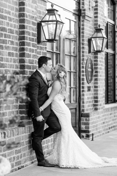 black and white of bride and groom kissing against brick