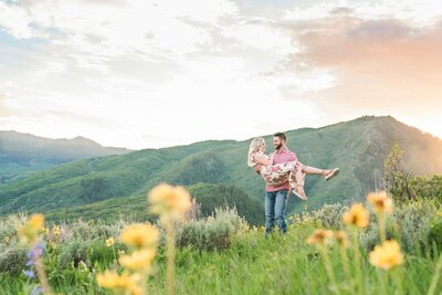 engaged couple at the top of utah mountains with wildflowers