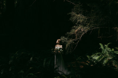 bride standing in forest