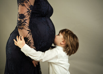 young-son-kissing-mothers-baby-bump