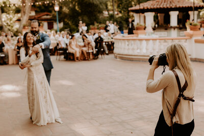 woman taking picture of bride and groom
