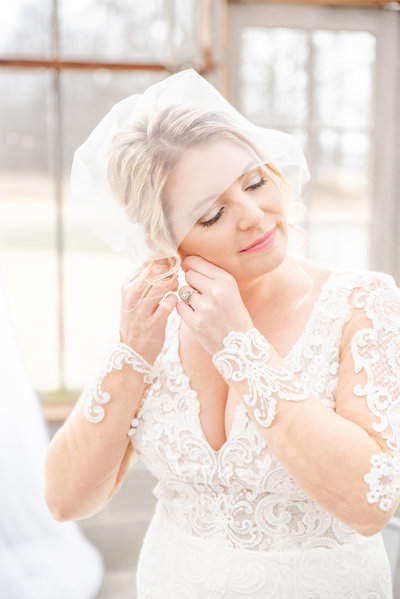 portrait of bride putting in her earrings on her wedding day