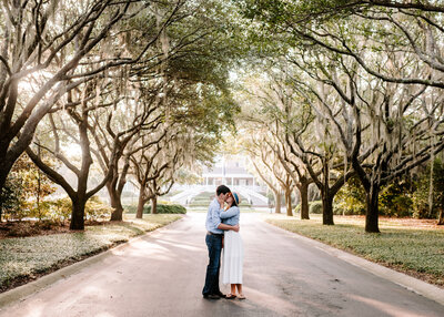 man and woman kissing under large trees while standing in long driveway