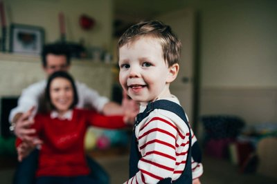 Relaxed photograph of toddler boy at home with parents in Ipswich