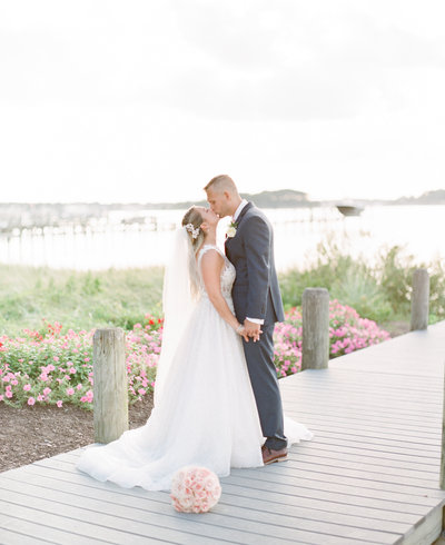 Bride and groom kiss on dock at Clarks Landing Yacht Club wedding