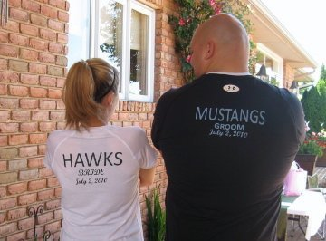 Megan and Dave wearing their engagement shirts featuring NHHS Hawks and CMW Mustangs