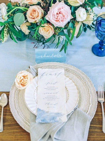 wedding invitation on reception plate with florals