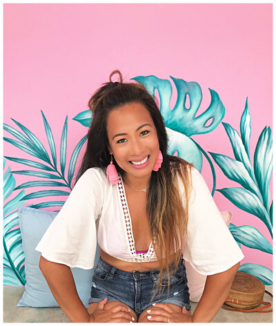 A pink background with a client smiling with her hands on her thighs smiling