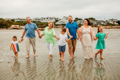family with grandparents walks on beach holding hands in boston
