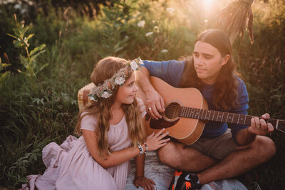 Young girl in a floral crown smiling at her father while he plays the guitar at sunset
