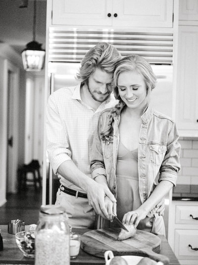 Couple cooking in kitchen for engagement session in Highlands