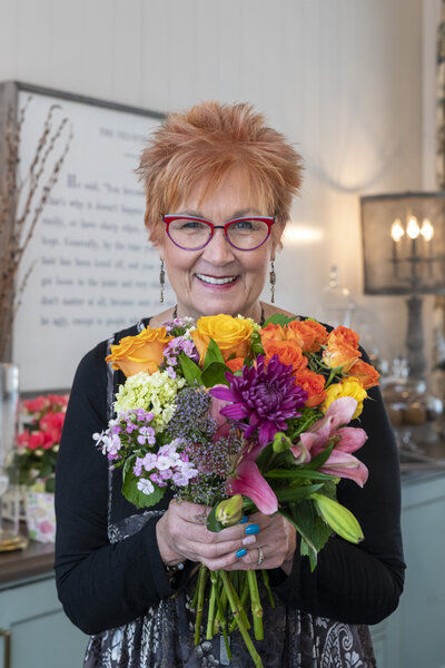 Jane Shine with bouquet of colorful flowers