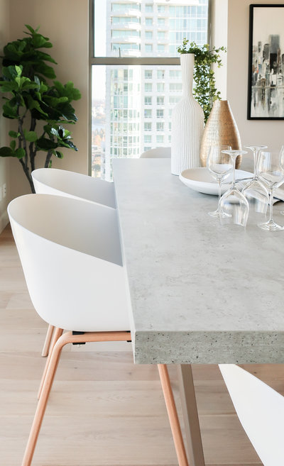 concrete dining table with white bucket chair