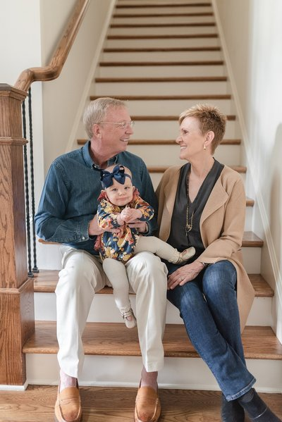 grandparents are sitting on the staircase in their house and holding their only granddaughter proudly