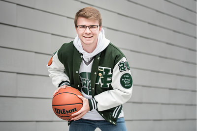 Senior guy wearing letterman jacket and smiling while holding a basketball at the Waterfront Park in Vancouver, Washington by Kim Blau Photography
