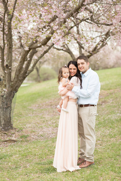 Family of three standing under a cherry blossom tree