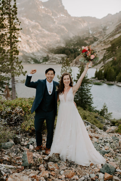 bride and groom with hands in the air while smiling with mountains in background
