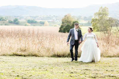 Camile and Austin walking in a field on their wedding day