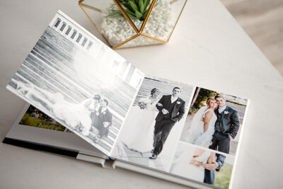Wedding photo album open on table with cactus terrarium