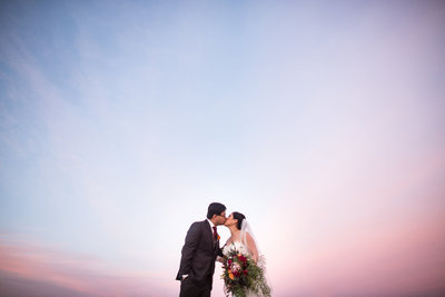 Bride and Groom kissing in front of pink sunset with big bouquet at Coronado Community Center