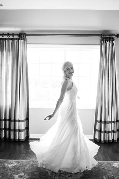 Happy bride twirls in her wedding gown on her wedding day