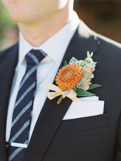 bride with orange floral boutonniere