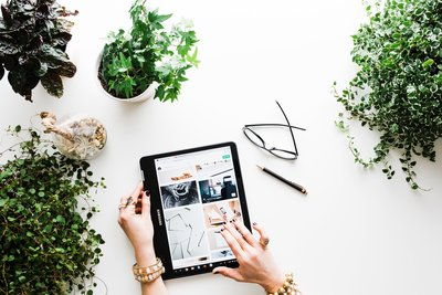 unsplash stock image that shows a woman scrolling through her iPad with a plant on the desk, glasses and a pen