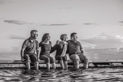 family of 4 embracing on dock in  a lake