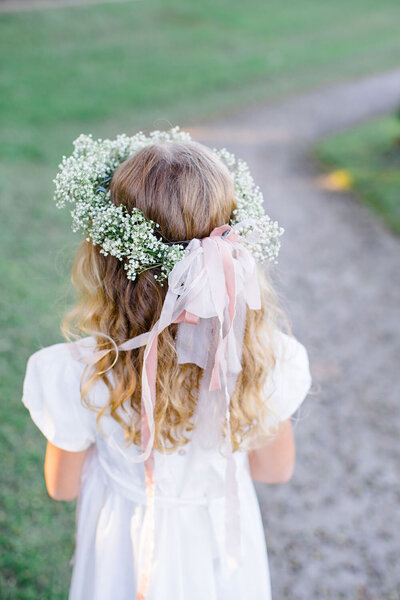 Baby's breath flower crown with trailing pink ribbons on a young flower girl