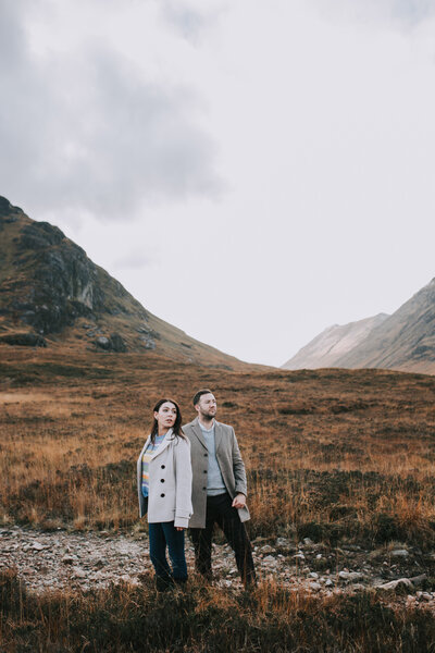 A couple standing in the middle of the mountain range of Glen Co Scotland