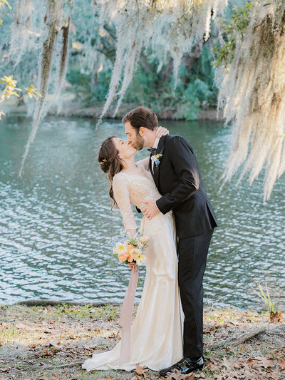 Just married couple kissing by a lake, with the bride holding out her wedding bouquet