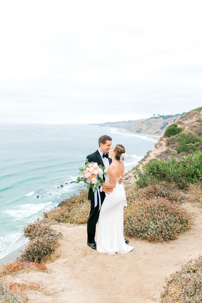 bride and groom portraits on cliff in San Diego