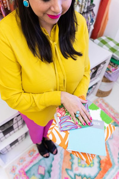 A woman in yellow sifts through fabrics and swatches.