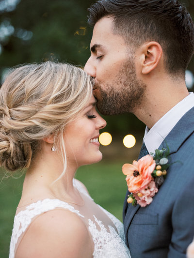 Groom kisses bride on forehead