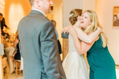 Washington DC live wedding painter Brittany Branson hugs a bride at the National Museum of Women in the Arts photographed by Adam Mason Photography