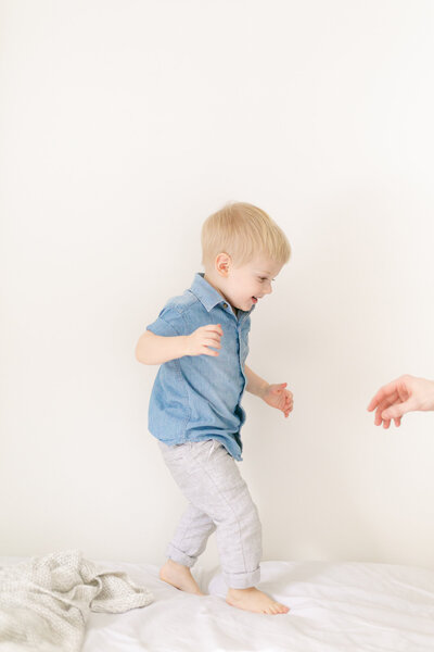 Relaxed portrait of a toddler jumping on the bed.