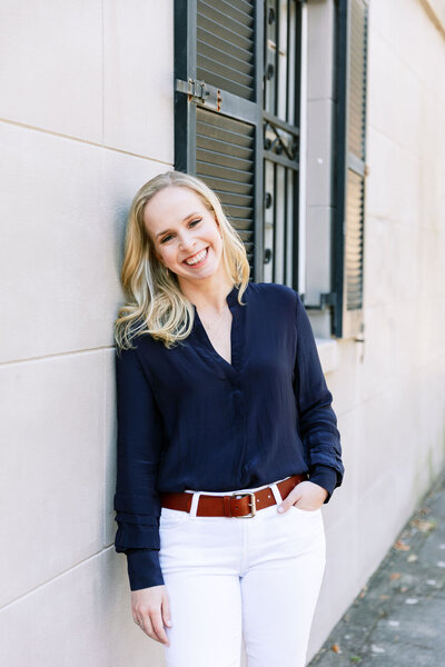Digital Grace Design owner, Sarah Blodgett, leans against wall outside and smiles wearing a blue silk blouse and white pants