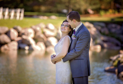 Bride and groom stand by the pond outside Wilderness Ridge Golf Club