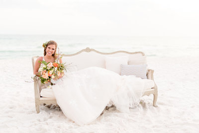 Bride sits on couch at beach.