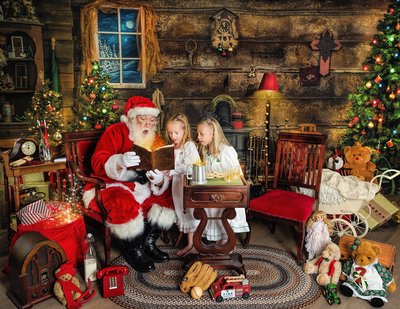 Santa looking at a book with two young girls in pajamas