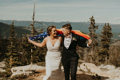 Couple with pride flag at Alpine Lakes High Camp elopement
