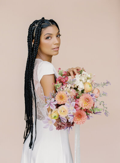Black bride with long braids holding a colorful bouquet