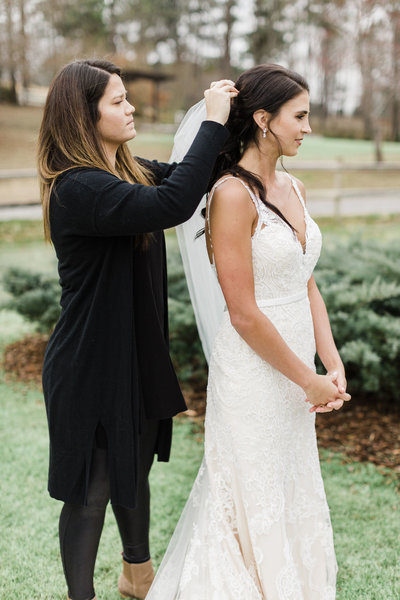 woman adjusting bride's veil
