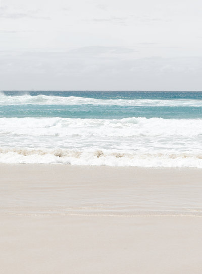 Pristine beach in Byron Bay, Australia. The water is teal and white and the sand is fine and soft. The waves are crawling onto the shore and it's a very peaceful scene.