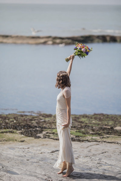 Bride waving to lifeboat crew at Tunnels Beaches wedding in Devon