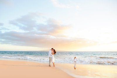 Mom and dad kissing while child runs on the beach at sunset