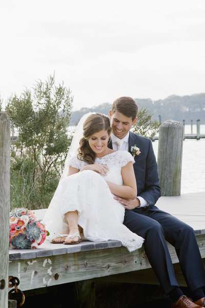 bride and groom sit on dock at clarks landing yacht club wedding
